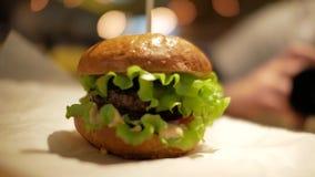 Hamburger classico su una tavola sulla carta pergamena Caffè degli alimenti a rapida preparazione