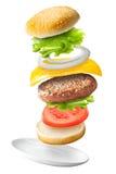 Hamburger classico volante su fondo isolato Fotografia Stock