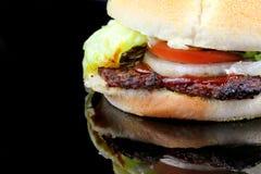 Hamburger close up. Hamburger with lettuce, tomato and onion on black glass Royalty Free Stock Image