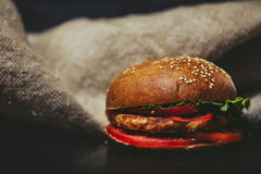 Hamburger close-up on the black table on the background of burla Stock Image
