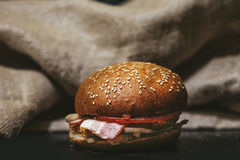 Hamburger close-up on the black table on the background of burla Royalty Free Stock Photos