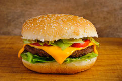 Hamburger closeup. Hamburger or cheeseburger closeup on a wooden background