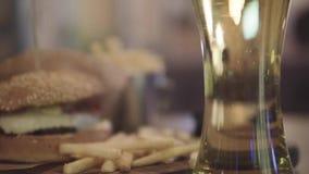 Hamburger com cerveja e fritadas na tabela vídeos de arquivo
