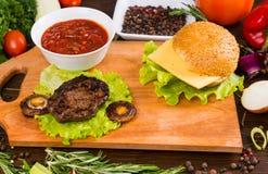 Hamburger com coberturas e os ingredientes frescos imagem de stock