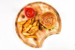 Hamburger com cunhas e souce no círculo de madeira Fotos de Stock Royalty Free