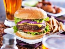 Hamburger com fritadas Fotografia de Stock Royalty Free