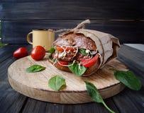 Hamburger com pão preto e tomates na tabela Fotografia de Stock Royalty Free