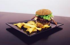 Hamburger con bacon e le patate dal lato fotografia stock libera da diritti