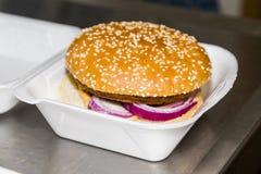 Hamburger con carne, verdure, ringsin della cipolla porpora un contenitore bianco di alimento Fotografie Stock Libere da Diritti