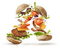 Hamburger con gli ingredienti di volo fotografia stock libera da diritti
