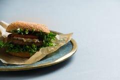Hamburger con gli ortaggi freschi, alimenti a rapida preparazione sani, fondo bluastro del vegano fotografia stock