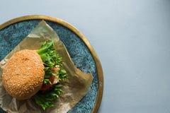 Hamburger con gli ortaggi freschi, alimenti a rapida preparazione sani, fondo bluastro del vegano fotografia stock libera da diritti