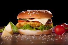 Hamburger con il pollo e formaggio, lattuga, cetrioli, pomodori e cipolle Fotografia Stock