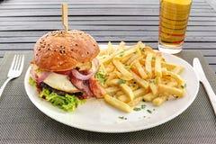 Hamburger con l'uovo fritto, il bacon e le patate fritte sul piatto bianco Immagini Stock
