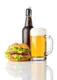 Hamburger con la bottiglia e la tazza di birra fredda su bianco Immagine Stock