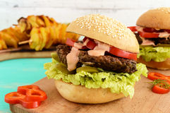 Hamburger con la cotoletta del fegato, i pomodori, i sottaceti, la lattuga, la salsa piccante e un panino molle con i semi di ses fotografia stock libera da diritti