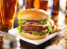 Hamburger con le fritture ed il panorama della birra Fotografie Stock
