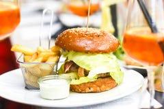 Hamburger con le fritture su un piatto in un restaura meravigliosamente servito fotografie stock