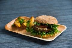 Hamburger con le patate al forno, fondo bluastro del vegano fotografia stock libera da diritti