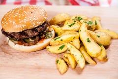 Hamburger con le patate dell'Idaho sul bordo di legno Fotografie Stock Libere da Diritti
