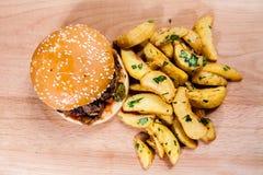 Hamburger con le patate dell'Idaho sul bordo di legno Immagini Stock