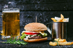 Hamburger con le patate fritte, birra su una tavola di legno bruciata e nera Pasto rapido L'hamburger casalingo consiste della ca Fotografia Stock Libera da Diritti