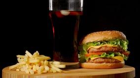 Hamburger con le patate fritte e un vetro con la cola del ghiaccio su un fondo rustico nero video d archivio