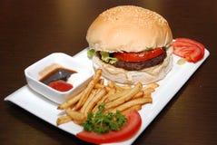 Hamburger con le patate fritte e le verdure, servite con i sauses immagine stock libera da diritti
