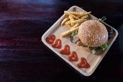 Hamburger con le patate fritte in piatto di legno fotografia stock