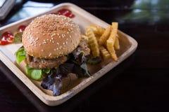 Hamburger con le patate fritte in piatto di legno immagini stock