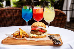 Hamburger con le verdure e patate e cocktail fotografie stock