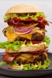 Hamburger con manzo, bacon, il pomodoro, il formaggio, la lattuga e la cipolla immagini stock libere da diritti