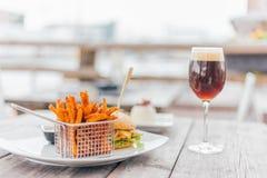 Hamburger con un Glas di birra Fotografie Stock