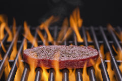 Hamburger Cooking on a Flaming Grill Royalty Free Stock Images