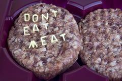 Hamburger crudo nel vassoio L'iscrizione della pasta riccia delle lettere - non mangi la carne fotografia stock libera da diritti
