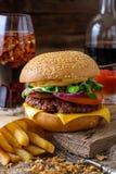 Hamburger délicieux avec des puces et soude sur la table en bois Photographie stock