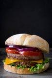 Hamburger délicieux avec du fromage de cheddar, la tomate, la laitue et l'oignon Noircissez le fond d'ardoise image stock