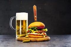Hamburger délicieux de boeuf sur un conseil en bois avec un verre de bière Photo stock