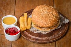 Hamburger délicieux sur le papier avec des sauces et des fritures Images stock