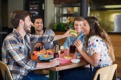 Hamburger de alimentation de jeune homme à l'ami dans le restaurant Photos libres de droits
