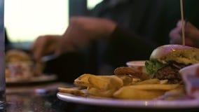 Hamburger de calorie avec des pommes frites, les gens mangeant à la table de café, déjeuner malsain images libres de droits