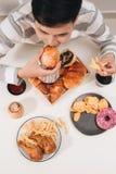 Hamburger de calorie avec des pommes frites, les gens mangeant à la table de café, déjeuner malsain photos libres de droits
