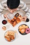 Hamburger de calorie avec des pommes frites, les gens mangeant à la table de café, u images libres de droits