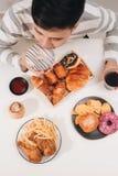 Hamburger de calorie avec des pommes frites, les gens mangeant ? la table de caf?, d?jeuner malsain image libre de droits