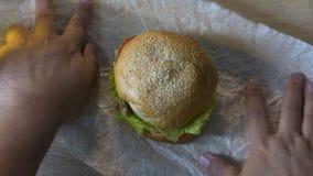 Hamburger de déroulement masculin sur la table à la maison, préparation pour le déjeuner, consommation malsaine banque de vidéos