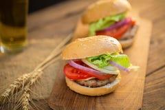 Hamburger de fromage avec de la viande grillée, fromage, tomate, sur le papier de métier Photos libres de droits