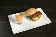 Hamburger de fromage de poulet, avec des sauces du côté photo libre de droits