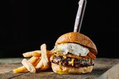 Hamburger de petit déjeuner avec un oeuf au plat sur la surface rustique foncée, horizo photo libre de droits