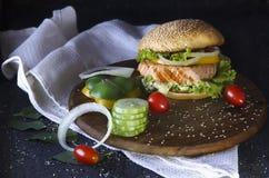 Hamburger de poissons sur un support en bois Photographie stock
