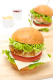 Hamburger de poulet avec des légumes, fromage sur un conseil en bois Images stock